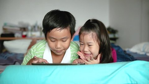 Asian children using digital tablet. Cute yonger sister kissing on cheek and cheering her brother near by, brother kiss her too. Cute boy playing games excitedly on touchpad and lying prone on bed.