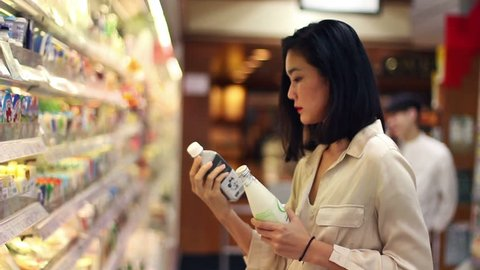 asian woman looking at groceries good at super market deciding what to buy.