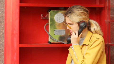 Young stylsh female person talking on phone in red call box yellow sunglasses leather jacket spring casual fashion calm serious face emotions proffesional woman calling in telephone booth film shoot