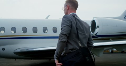 Businessman walking towards private jet on a runaway 4k
