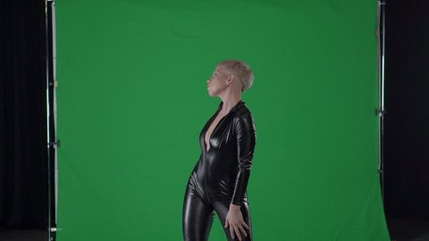 Modern dancer girl is performing sensual dancing movements. She is looking in camera and standing in background of chroma key green screen