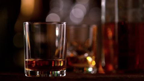 Super slow motion of falling ice cube into whiskey glass. Filmed on cinema slow motion camera, 1000fps