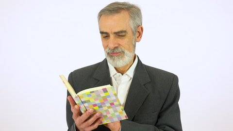 An elderly man reads a book - white screen studio
