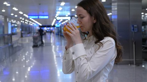 Woman drink fresh orange juice, half length shot in empty airport hall, blurred background. Lady hold plastic glass and make gulp of freshly squeezed drink from vending machine.