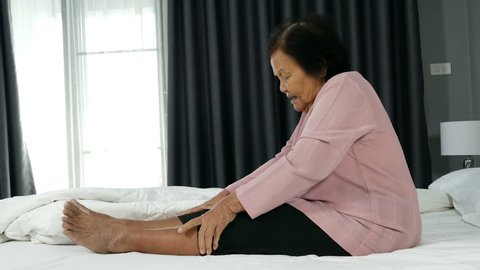 4k of senior woman with leg pain in a bed
