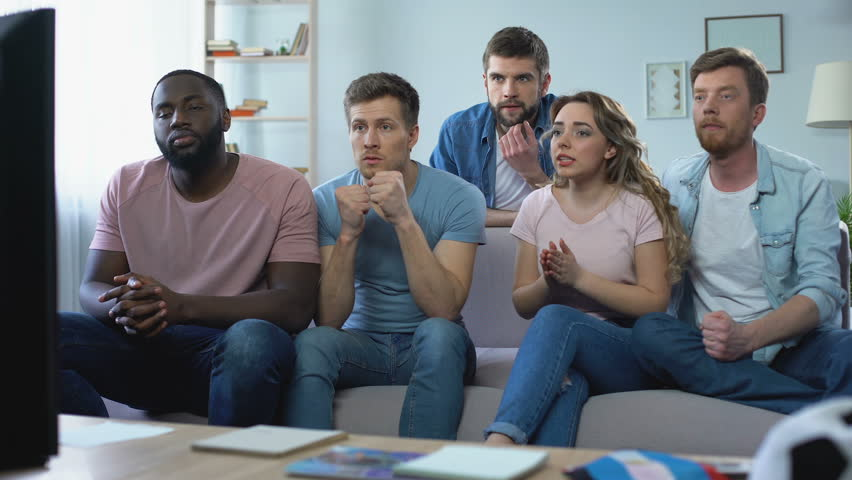Multi-ethnic group of friends watching football game at home, celebrating goal | Shutterstock HD Video #1012331000