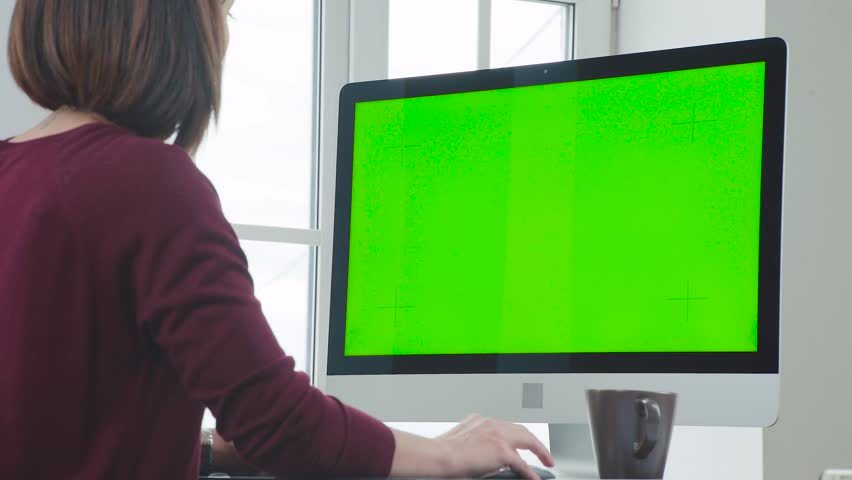 Taken from the shoulder of a young girl sitting in front of a monitor. Woman is working in the office in front of a computer. Back of a woman with a short haircut, she sits in front of the monitor. | Shutterstock HD Video #1012336820