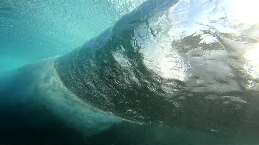 Blue surfing wave breaking over coral reef, slow motion surface and underwater view | Shutterstock HD Video #1012339610
