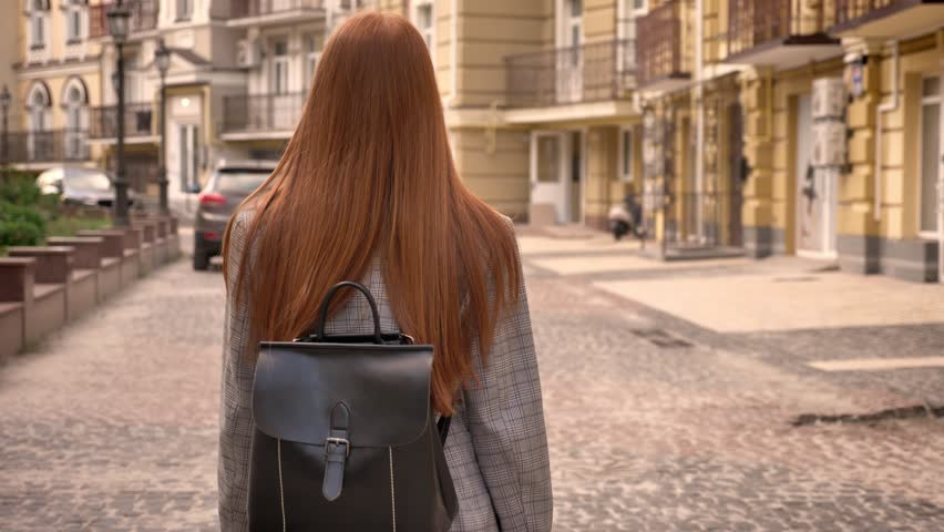 Young woman with long ginger hair walking on city street and looking back, holding backpack, urban street background, back view | Shutterstock HD Video #1012349360