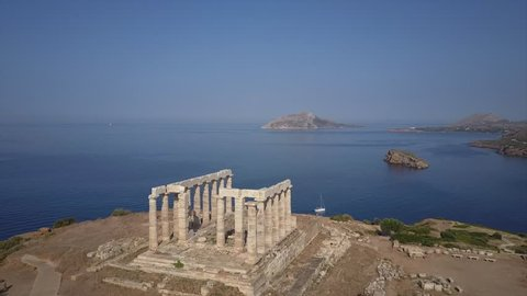 Cape Sounion Greek temple of Poseidon. 4k revealing drone shot over building. ocean and sailing boat in background