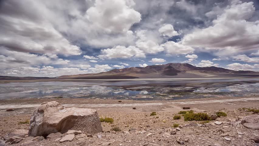 Timelapse of moving clouds reflected in salt lake (Laguna Salta) in the Atacama Desert in Chile with a prominent stone in foreground and mountain peak in background
