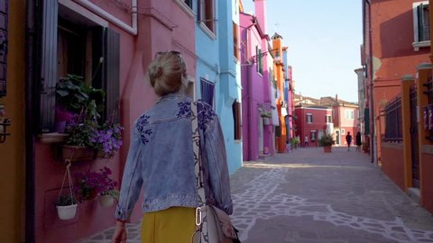 Young woman walking in colorful streets of Burano, Italy during sunset