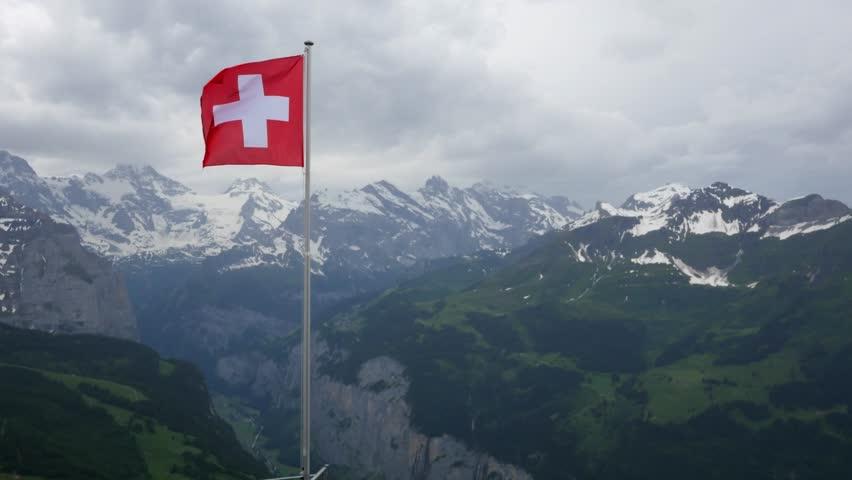Swiss flag fluttering in the Alps   Shutterstock HD Video #1012369130