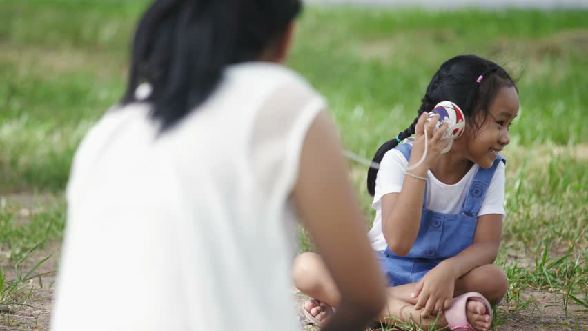 Asian family, mother and daughter doing string phone play activities tie rope at the park.