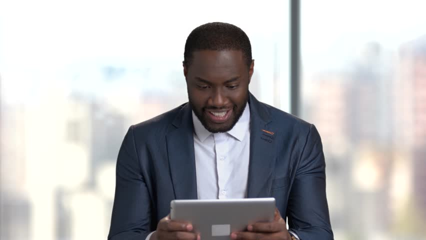 Funny dark-skinned businessman playing online game. Afro-american man in business suit playing game on pc tablet. Break at work. | Shutterstock HD Video #1012401740