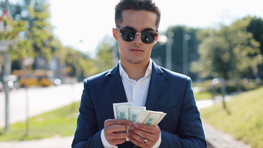 Young happy businesman in sunglasses and a suit counting money and walking in the street. He selebrating his successful win with a lot of dollars