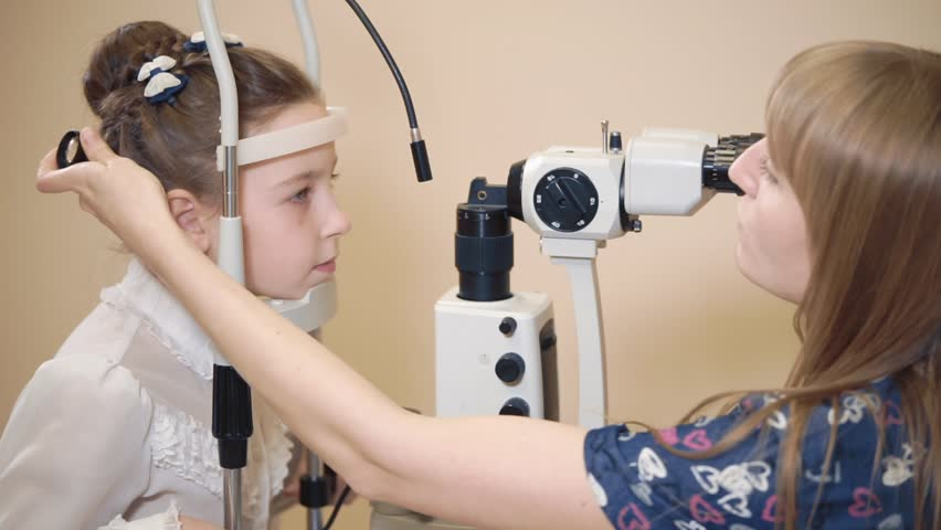 Ophthalmologist is directing face of schoolgirl in a fixing tapes. She is making biomicroscopy inspection of her eyes #1012424360