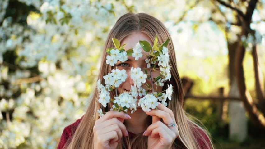 Portrait of charming Caucasian girl with attractive smile hiding behind flowering twigs. Blue-eyed young woman looking at camera, smiling on background of garden. Spring. Close-up.