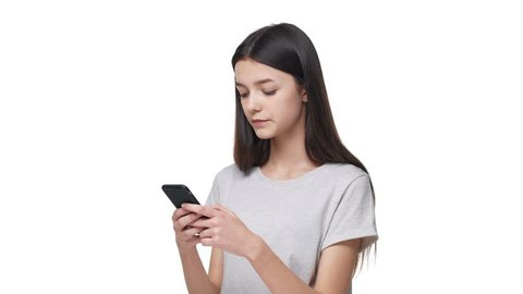 Portrait of happy teenage woman 20s wearing casual clothing holding smartphone and typing text message or chatting, isolated over white background. Concept of emotions