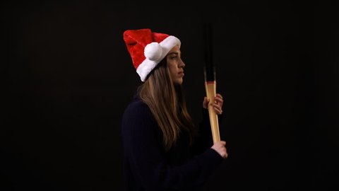 A girl with a Christmas hat holding a baseball bat