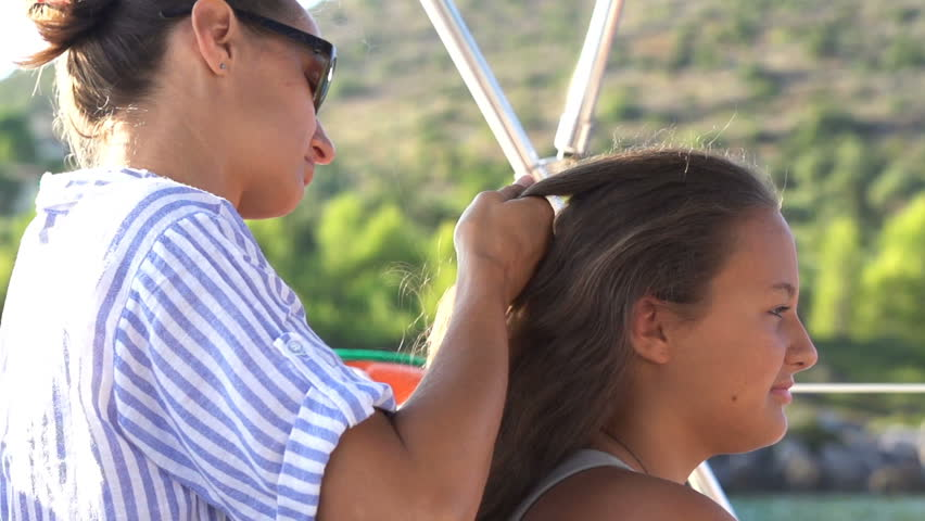 Family sailing boat on sea, woman braiding her daughter's hair  | Shutterstock HD Video #1012460360
