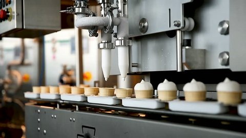 Filling of wafer cups with ice cream. Ice cream production line. Vanilla ice cream. Ice cream production line.
