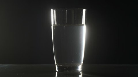 Effervescent tablet falls on a bottom of a glass