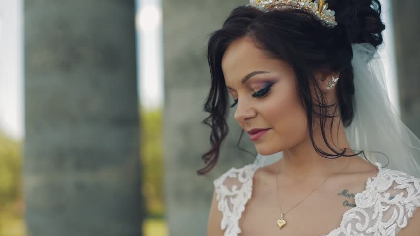 Beautiful and lovely bride standing near old columns | Shutterstock HD Video #1012519100