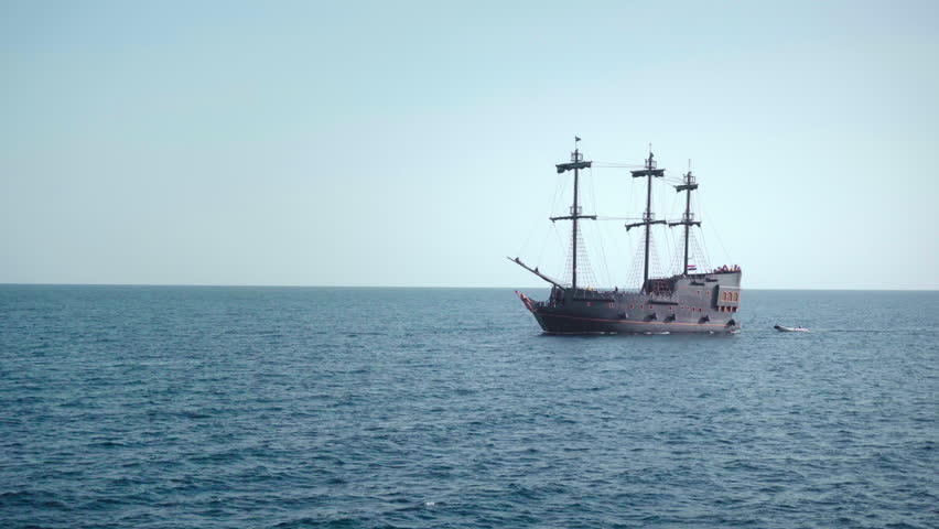 A pirate sailboat in the blue waters of the ocean. near view.