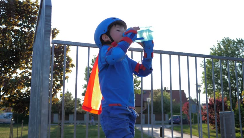 Rollerblading kid drinks pure water from bottle on open air in backlight close-up