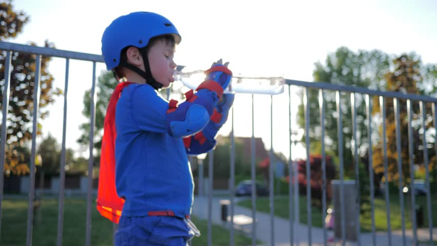 sports child in helmet and rollers drinks pure water from plastic bottle outdoors in backlight
