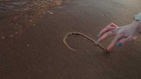The drawing of heart on the sand beach.