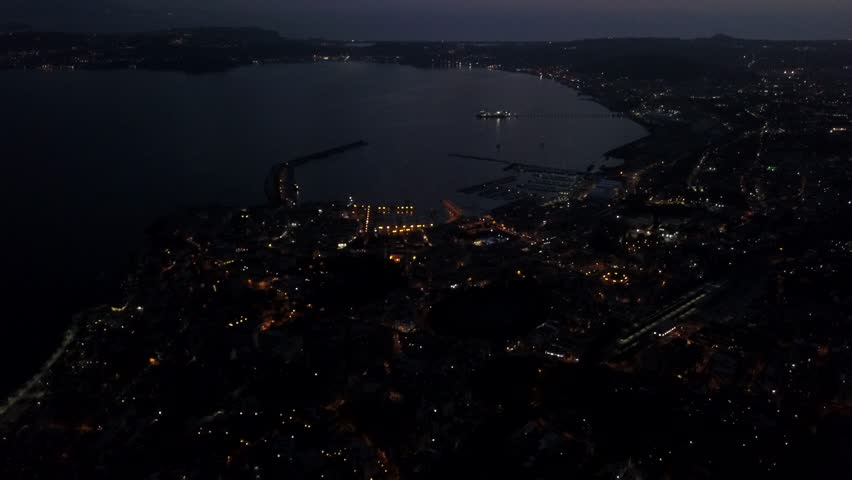 Aerial drone video of the Italian city of Pozzuoli at night.  It is a beautiful coastal city and tourist destination next to Naples.  Drone flies over the water with the city lights reflecting.