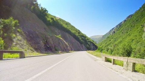 POV drive across beautiful nature with green trees and steep mountain slopes, curvy asphalt road, sunny day clear blue sky horizon, car travel gopro point of view
