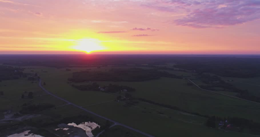 Amazing aerial view of beautiful sunset over the small country town. Green fields and tall trees. Nature / town landscape.   Shutterstock HD Video #1012592990