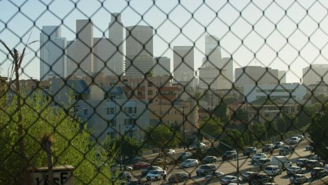 Skyscrapers of Los Angeles withing traffic seen in the foreground through a wired fence (focus in)