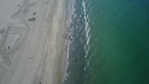 Aerial footage of empty, desolate beach in Southern California's Belmont Shore area of Long Beach