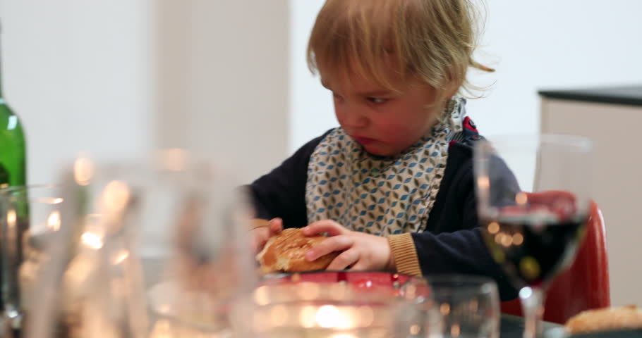 Baby toddler eating burger for dinner. Young boy eating hamburger for the first time for supper   Shutterstock HD Video #1012661510