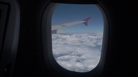 View of the clouds and the Himalayas from the window of the plane. Journey to the Himalayan Mountains.