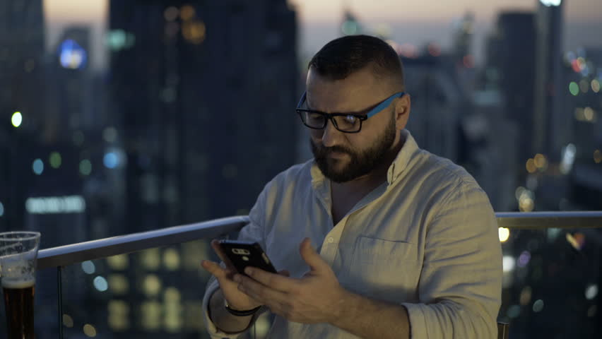 Man sitting in skybar at night and browsing internet on smartphone  | Shutterstock HD Video #1012677860