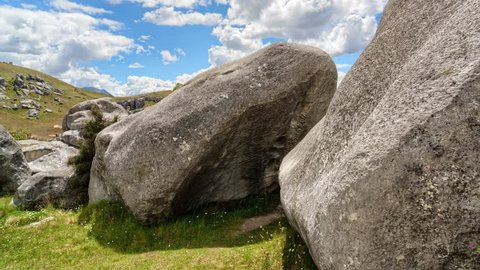 Hdr timelapse/hyperlapse of new zealand grasslands showing rock formations  made famous in the lord of the rings trilogy  features slow panning motion  with cloud motion set against a bright blue sky