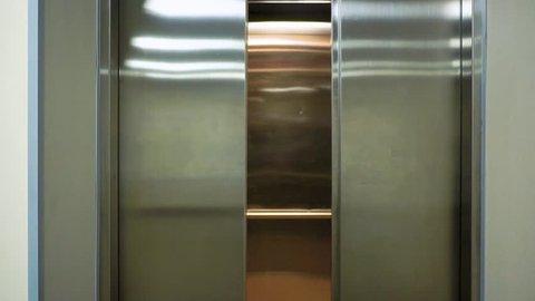 The elevator doors open. Opening the door is an elevator. Metal doors smoothly open.