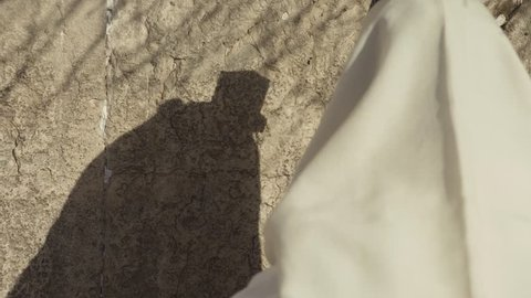 A shadow of a man Pray at the Western Wall in Jerusalem
