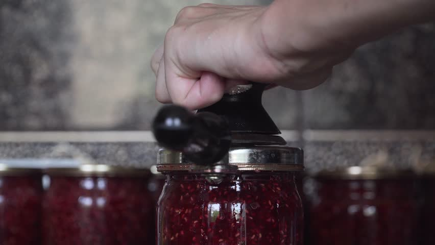 Preservation of raspberry jam with spanner to save for winter