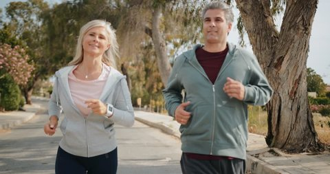 Active senior husband and wife having fun doing cardio exercise and running together outdoors