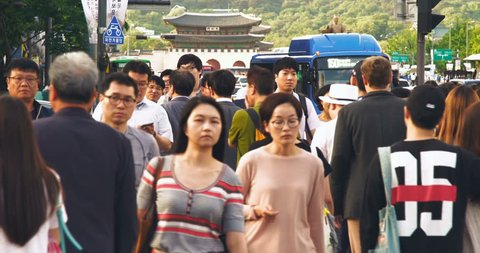 Crowd of people walking during the rush hours with Gwanghwamun Plaze in background, Seoul, South Korea