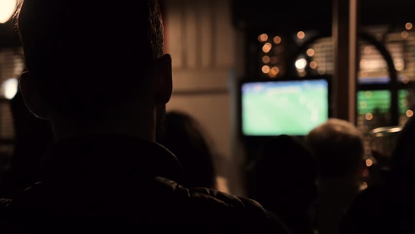 Man watching a football game on TV in a bar | Shutterstock HD Video #1012778030