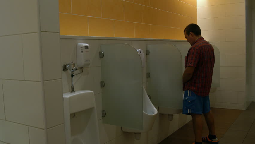4k00 12a Man Uses A Urinal In The Toilet