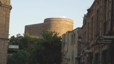 Far look of Maiden Tower in Old City, Baku Azerbaijan. Top of the Maiden tower is visible the rest is covered by trees