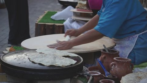 Old lady roll dough with stick and putting meat inside as she preparing street food in Old City in Baku Azerbaijan. She is preparing national food called Qutab.